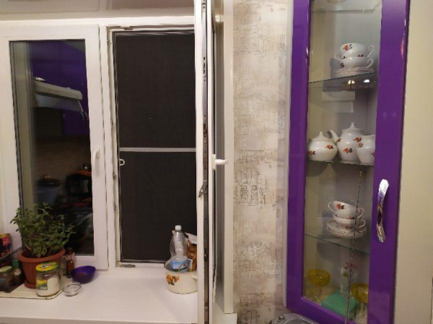 Стандартное пластиковое окно, рядом с ним — шкафчик для посуды