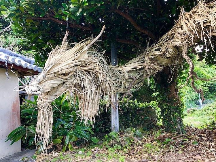 Скульптура гигантского японского дракона из листьев пальмы и дерева