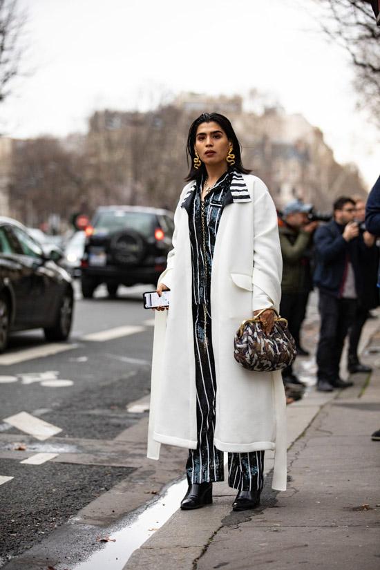 Девушка в белом длинном пальто, черный костюм в полоску и ботильоны