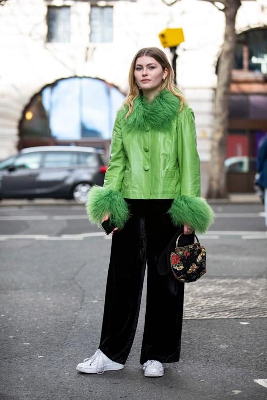 Девушка в зеленой куртке с перьями, черные широкие брюки и белые кеды