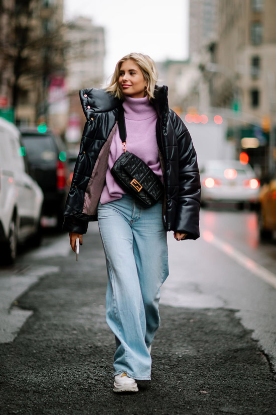 Девушка в широких голубых джинсах, фиолетовая водолазка и черный пуховик