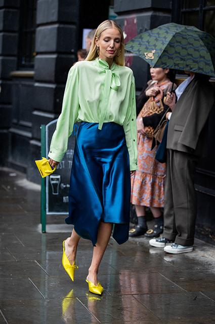 Девушка в синей шелковой юбке, прозрачная блузка и желтые туфли