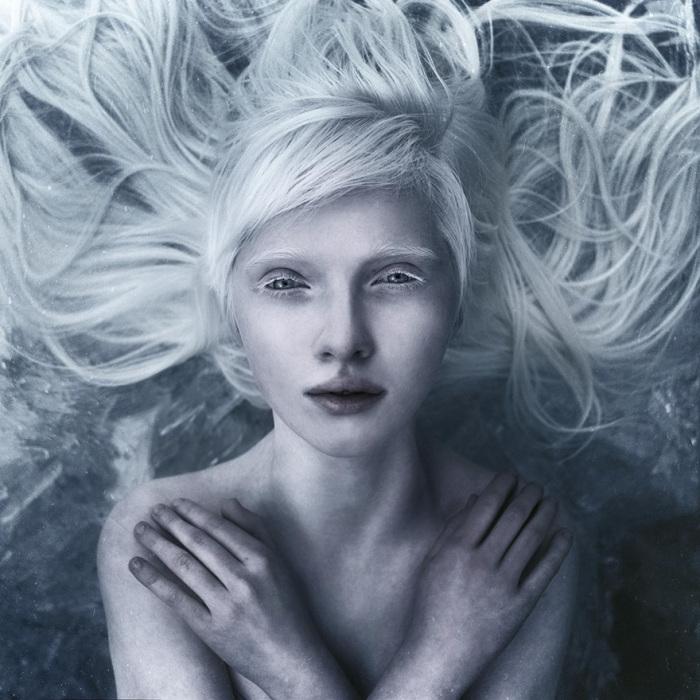 Изображение замерзшей девушки с льдинками на волосах.