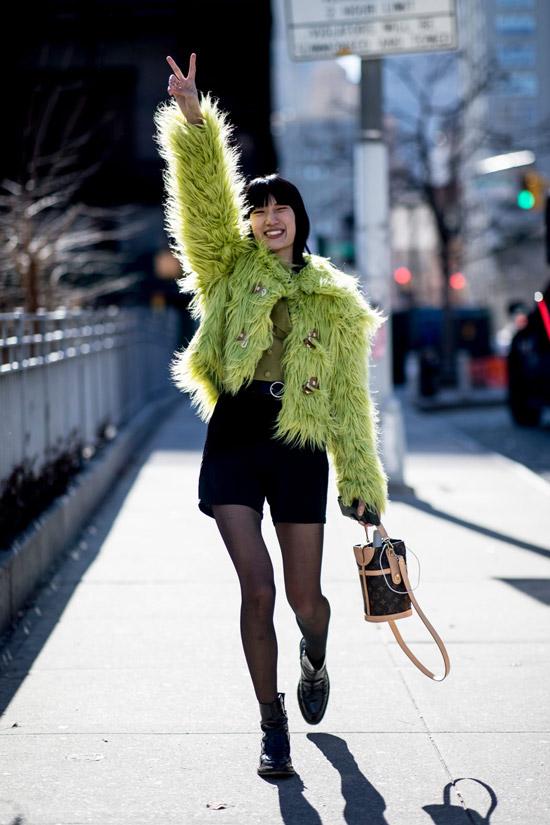 Девушка в черных шортах, зеленая куртка с перьями и черные ботинки