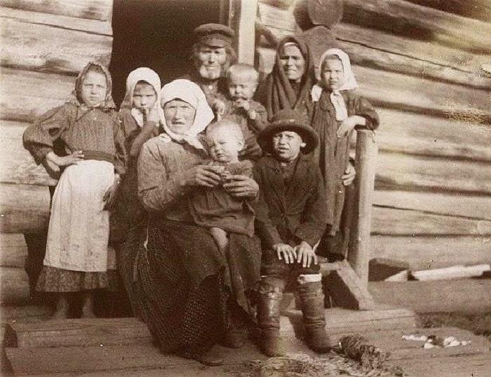 Многодетная семья возле избы, 1912 год. Автор фотографии: неизвестен.