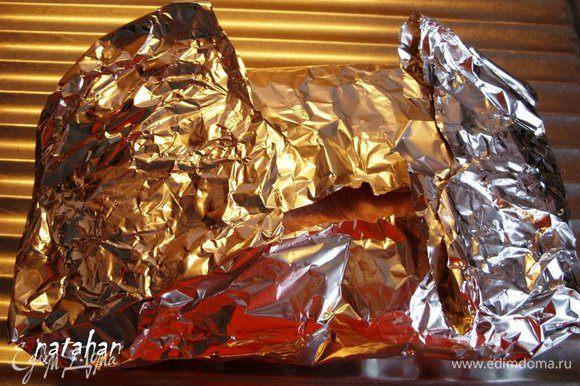 Расстелить на столе алюминиевую фольгу, смазать растительным маслом и аккуратно перекатить на неё ветчину с целлофановой плёнки. Завернуть в фольгу ветчину .
