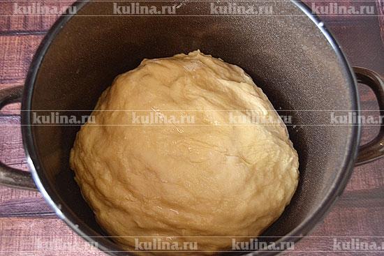 Затем продолжаем вымешивать эту вязкую массу на столе, присыпанном мукой, добавляя, если нужно муку на подсып. Стараемся не добавлять муки слишком много, чтобы не отяжелить тесто. После замеса на столе возвращаем тесто в кастрюлю, добавляем растительное или сливочное масло и еще раз переминаем тесто с маслом.
