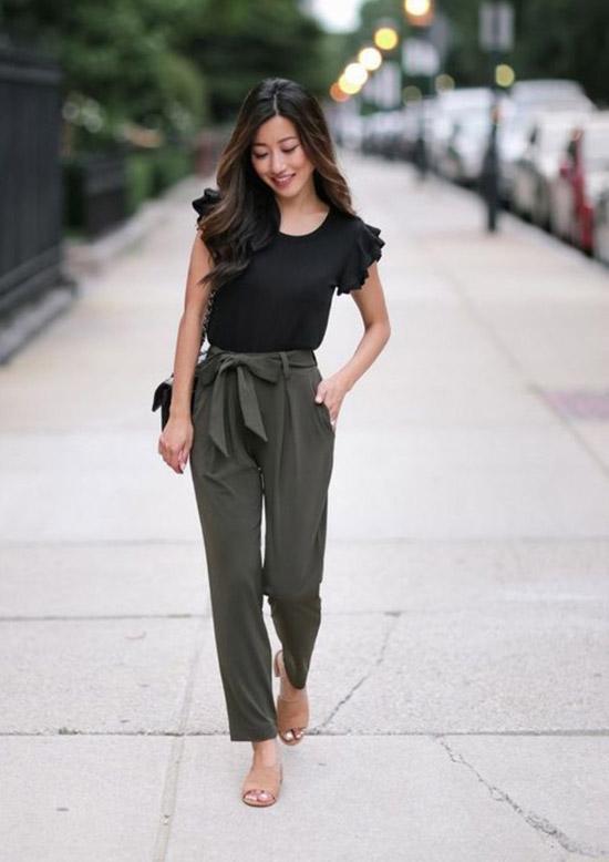 Девушка в брюках с поясом, черный топ и босоножки на толстом каблуке
