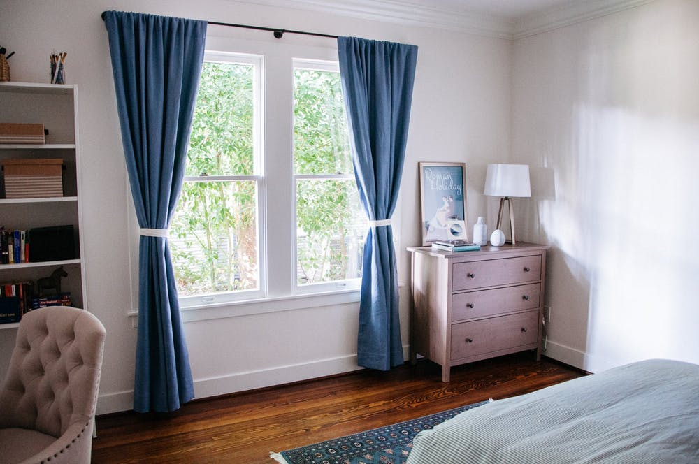 Синие шторы и коврик как яркие элементы декора в элегантном интерьере белой спальни