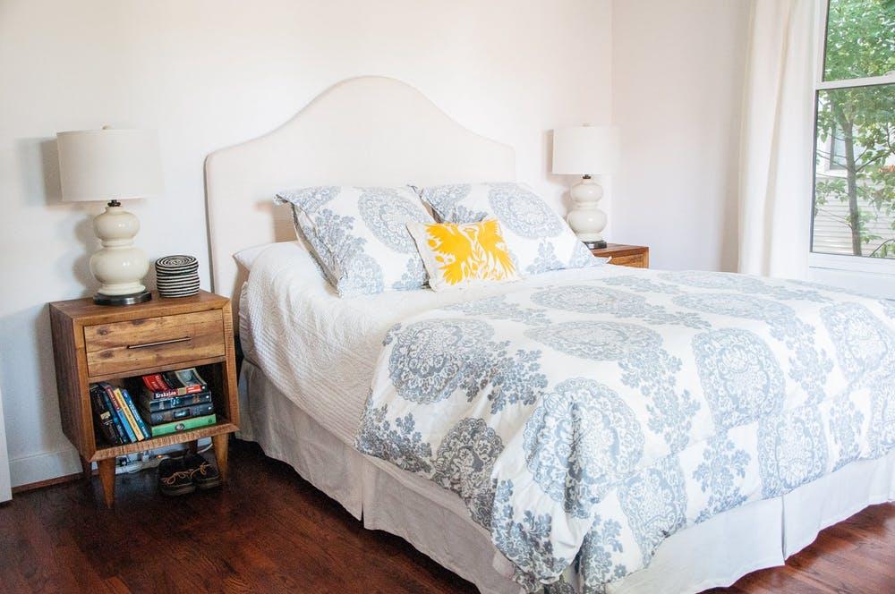 Элегантный интерьер белой спальни с винтажными прикроватными тумбочками