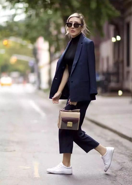 Девушка в черном брючном костюме, белые кеды и сумочка