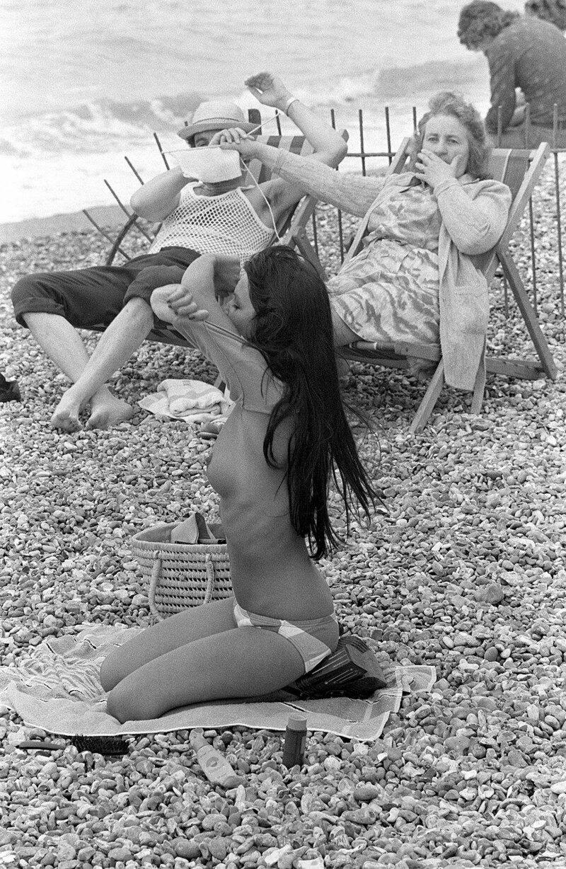 Женщина загораживает обзор мужу, чтобы тот не смотрел на раздевающуюся на пляже девицу. история, ретро, фото