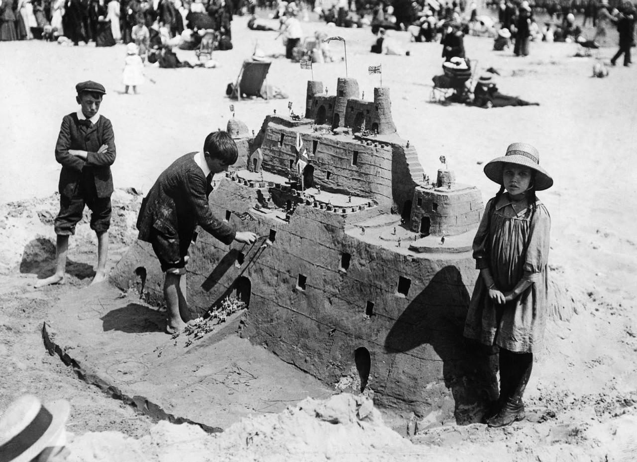 Дети строят песочный замок. Уэймут, Англия, примерно 1913 г. 100 лет назад, 20 век, архивные снимки, архивные фотографии, пляж, пляжный отдых, черно-белые фотографии, чёрно-белые фото
