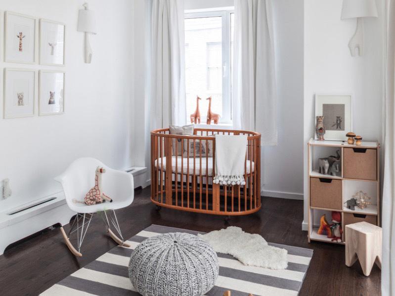 Белые стены, темный пол и овальная кроватка с полосатым ковром
