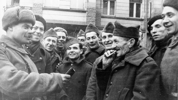 Советский солдат угощает папиросами освобожденных французских военнопленных. Третий Рейх. 1945 год.