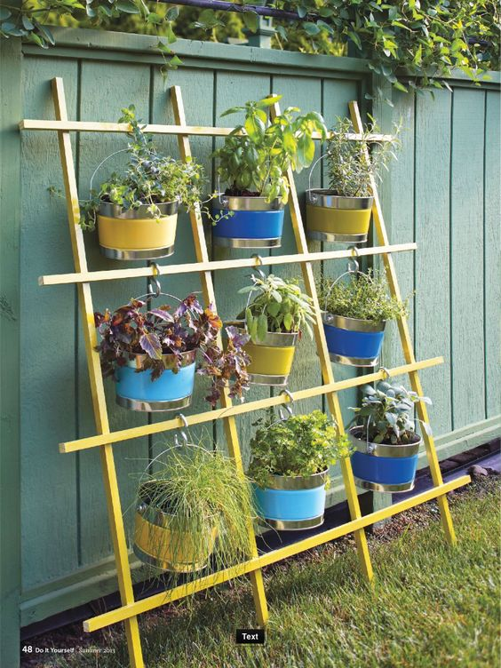 What a great idea for a verticle herb garden using a trellis, buckets and S hooks.: