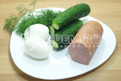 Огурцы и зелень промыть и обсушит. Яйца сварить вкрутую, колбасу нарезать кубиками.