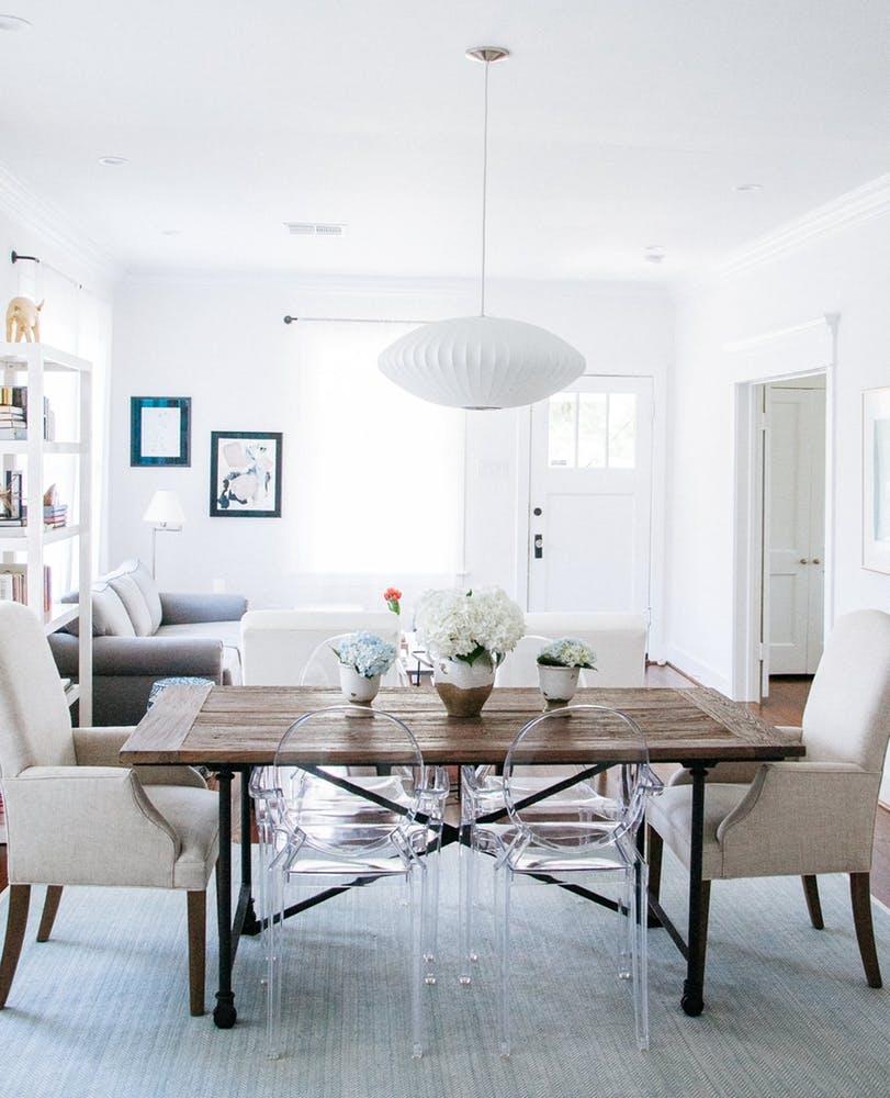 Элегантный интерьер белой гостиной с дизайнерским светильником