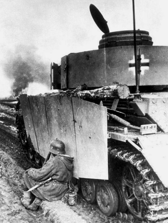 """Немецкий солдат укрывается за бронёй танка Pz.IVJ из 5-го танкового батальона 5-го танкового полка СС дивизии """"Викинг"""". Венгрия, 1945 г. Великая Отечественная Война, архивные фотографии, вторая мировая война"""