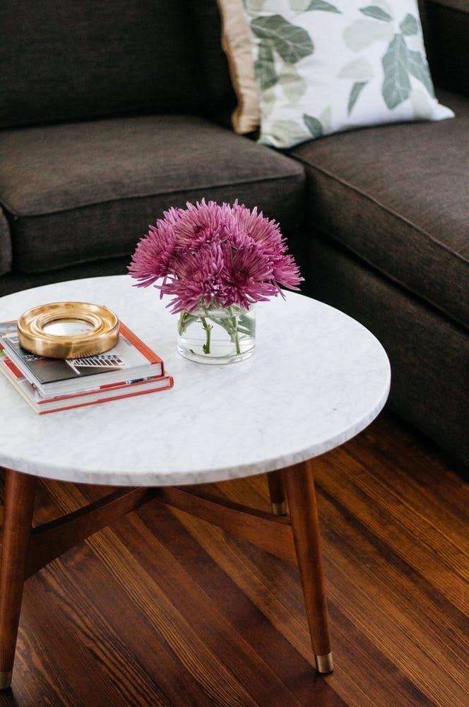 Элегантный интерьер квартиры - журнальный столик с круглой столешницей и деревянными ножками