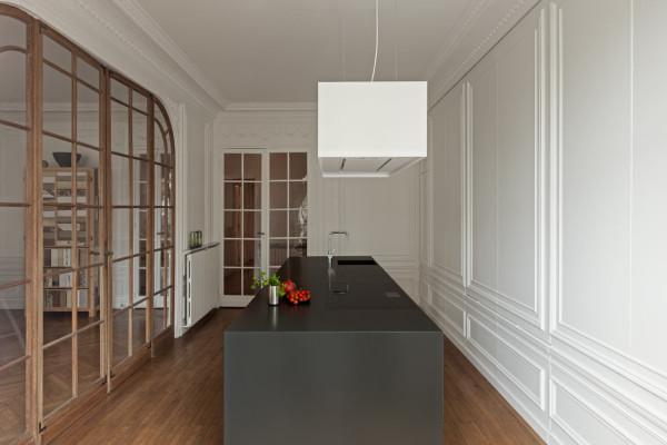 Белоснежная кухня с большим черным столом посередине.