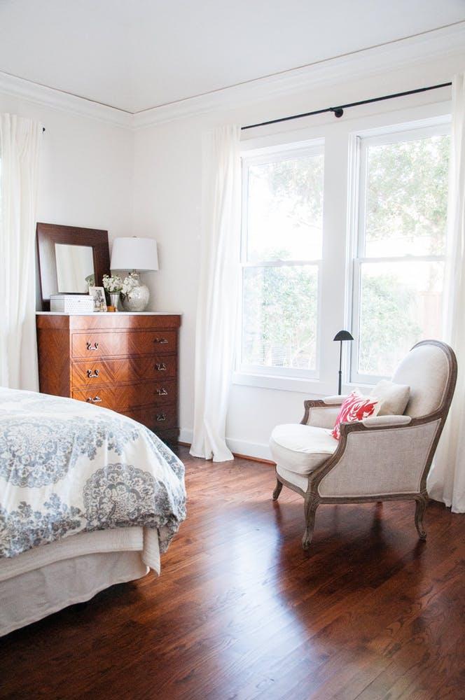 Элегантный интерьер белой спальни с деревянным комодом и креслом в классическом стиле