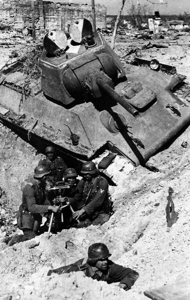 Немецкие миномётчики ведут бой в воронке от взрыва возле подбитого советского танка Т-34-76. Сталинград, октябрь 1942 г. Великая Отечественная Война, архивные фотографии, вторая мировая война