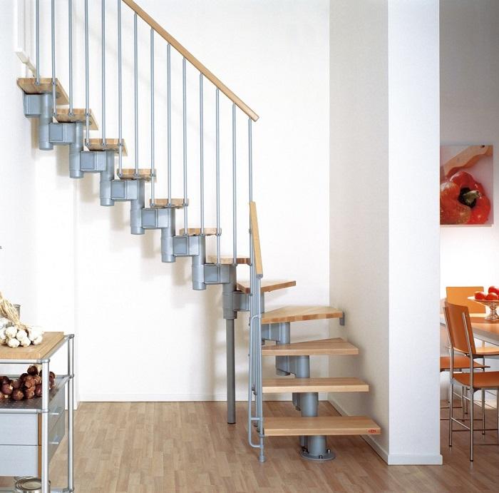 Лестница со ступенями, выполненными из лакированной древесины, и лаконичными металлическими перилами идеально вписалась в интерьер загородного дома.