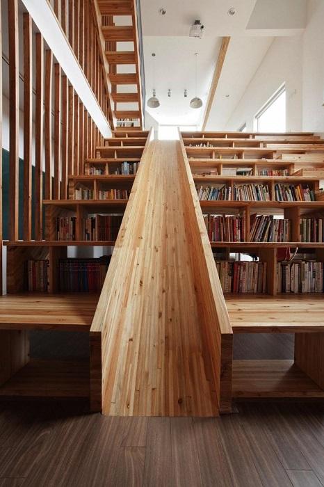 Необычная деревянная лестница со встроенными полками для книг и детской горкой.