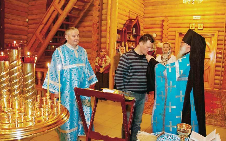 Роман Романенко целует складень во время благословения на полет