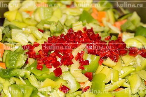 Острый перец очистить от семян, измельчить и добавить к овощам.