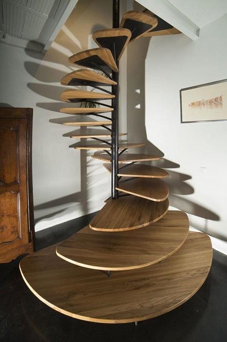 Роскошная винтовая лестница со ступенями оригинальной формы, выполненными из тёмной породы древесины.