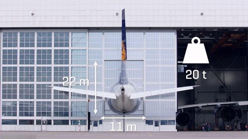 Раздвижные ворота в мюнхенском аэропорту с торчащим наружу хвостом самолета