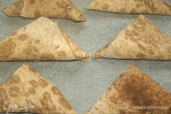 На застеленный пекарской бумагой противень кладем треугольники из лаваша. Отправляем в заранее разогретую до 180°C духовку на 7–10 минут.