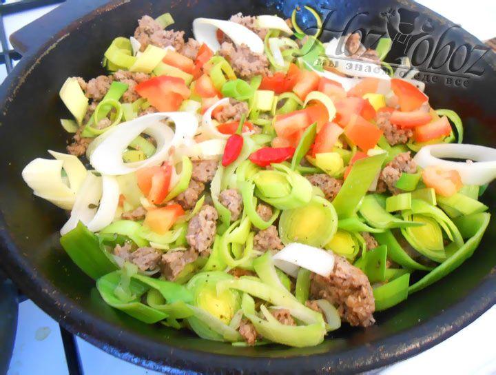 Когда лук станет полупрозрачным, добавьте на сковороде помидоры и жарьте еще 1-2 минуты