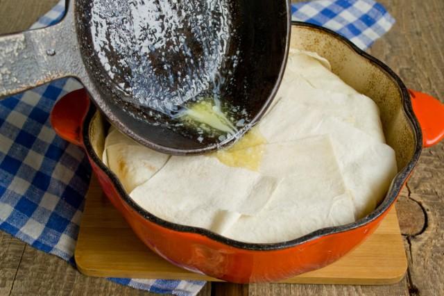 Заворачиваем края лаваша внахлёст, поливаем маслом