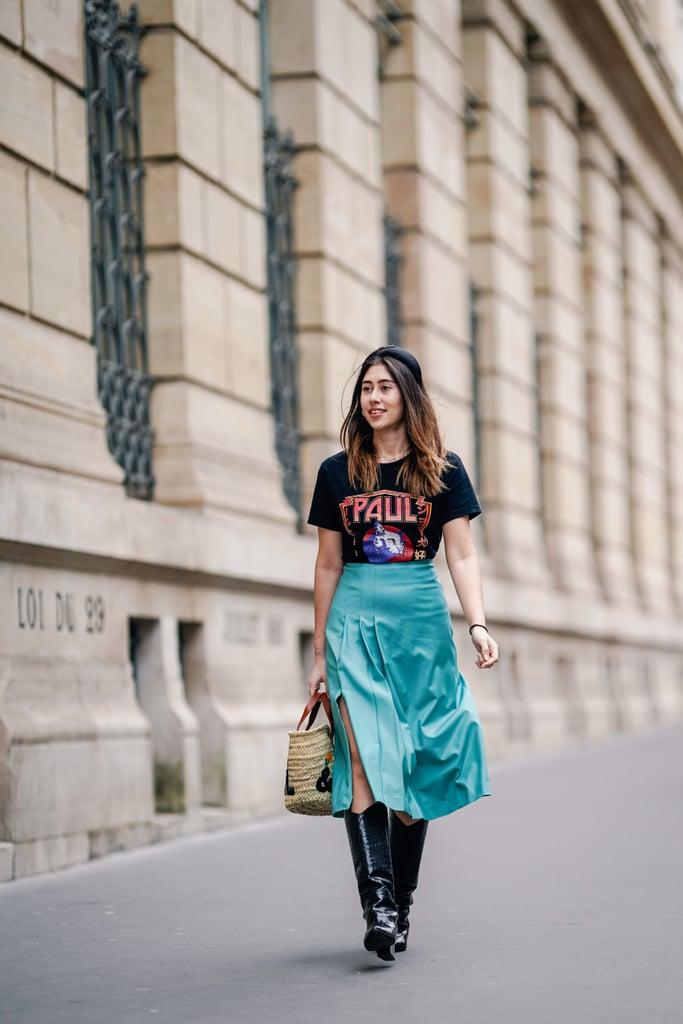 Девушка в зеленой юбке миди, черная футболка с принтом и сапоги
