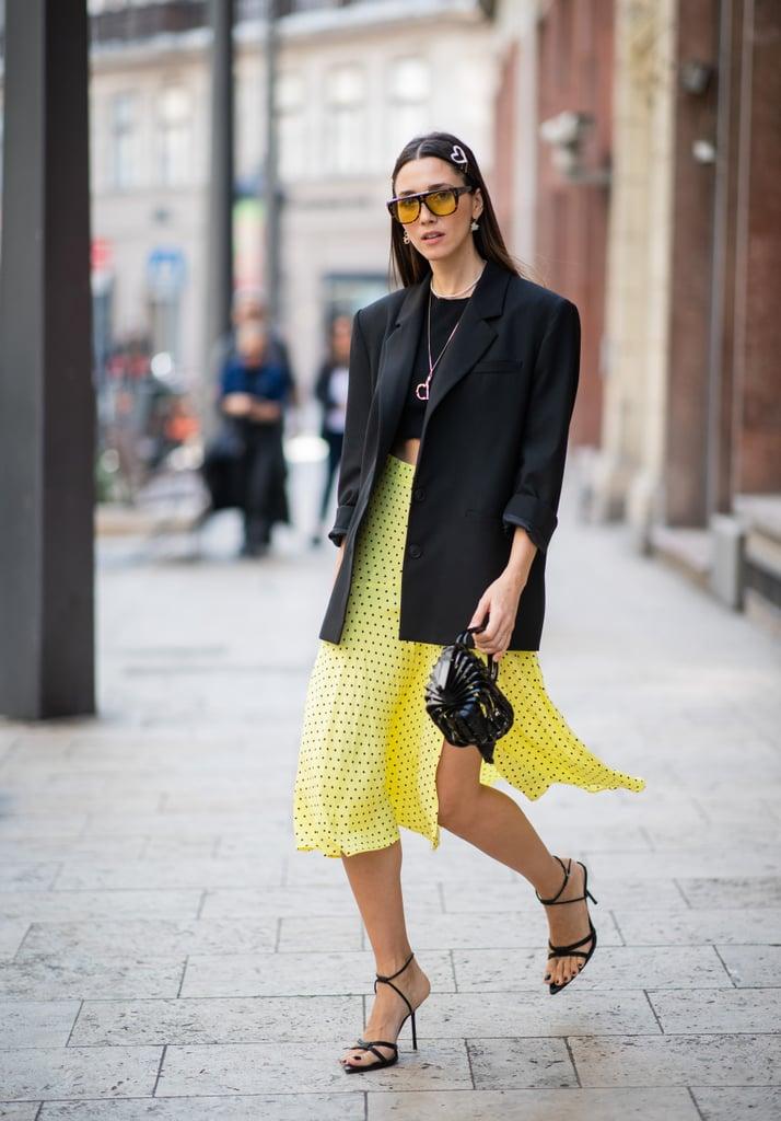 Девушка в желтой юбке миди, черный жакет и босоножки