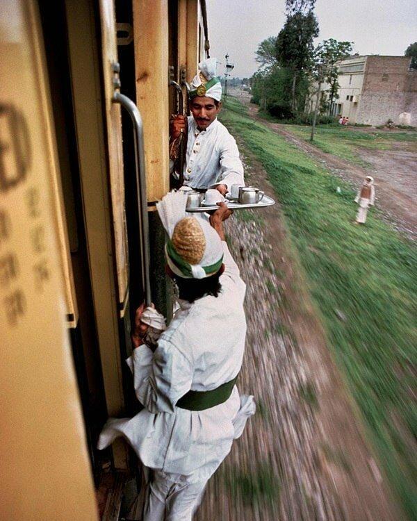 Официанты передают друг другу утренний чай между вагонами на железной дороге в Пакистане, 1983 год знаменитости, исторические фотографии, история, редкие фотографии, фото