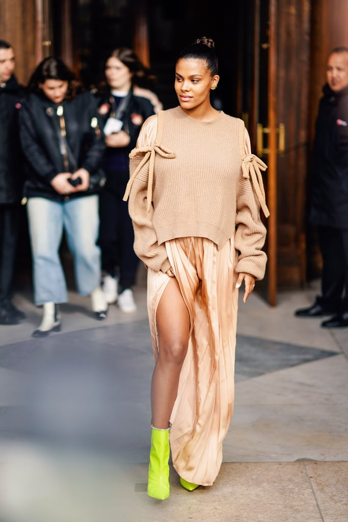 Девушка в шелковой юбке миди, бежевый свитер и зеленые ботильоны