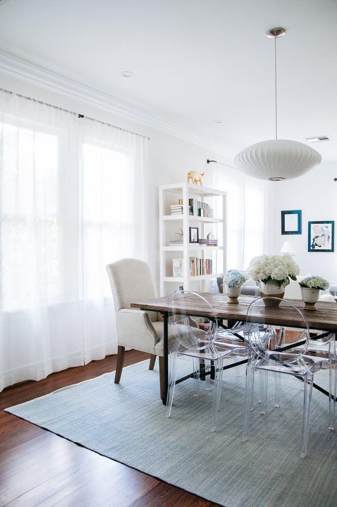 Элегантный интерьер квартиры - пластиковые прозрачные стулья с круглой спинкой в гостиной