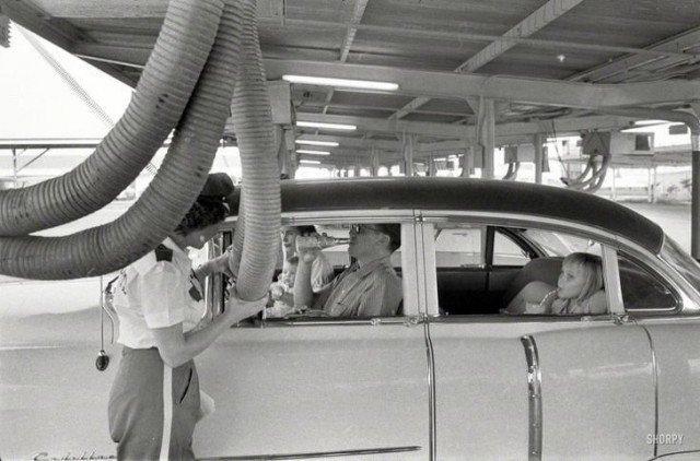 Холодный воздух подается в машину, пока ее пассажиры наслаждаются едой в ресторане формата drive-in. Хьюстон, 1957 год история, ретро, фотографии