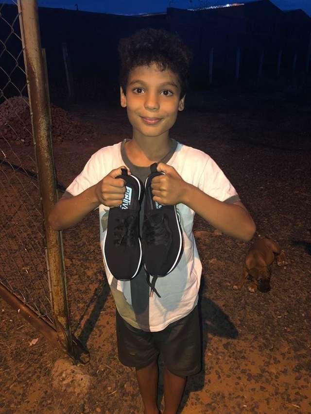 мальчик держит обувь в руках