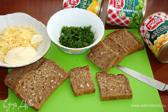 Теперь займемся зеленой «полянкой» для наших поросят. Для этого ломтики хлеба разрезать пополам. Сыр натереть на мелкой терке, к нему добавить зубчик чеснока, пропущенного через пресс и 3 ст. л. майонеза и перемешать. Зелень укропа мелко нашинковать. Хлеб можно взять любой, по вкусу. У меня хлеб злаковый, потому что мне кажется, что такая основа-полянка будет еще вкуснее.