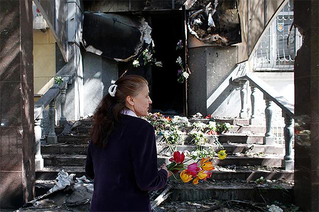 Кто-то несёт цветы к уничтоженному пожаром зданию местного управления МВД Украины.