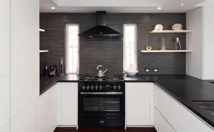 Интересное сочетание белоснежных поверхностей кухонных шкафов и черных глянцевых столешниц.