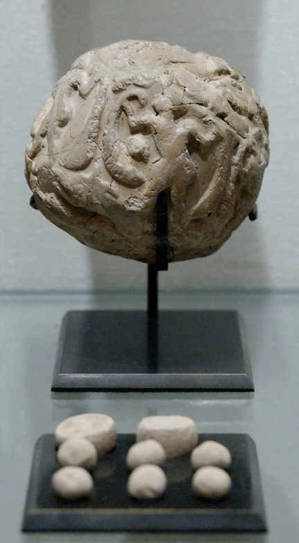 A bulla (or clay envelope) and its contents on display at the Louvre. Uruk period