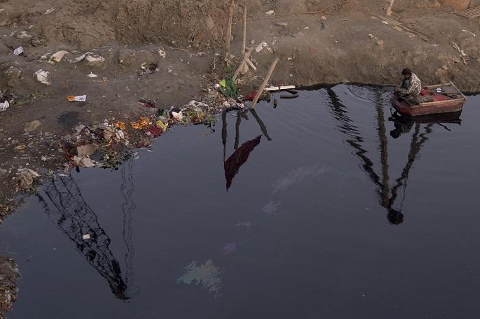 Вдоль реки можно увидеть горы мусора, а сквозь загрязненную воду даже у самого берега не видно дна.