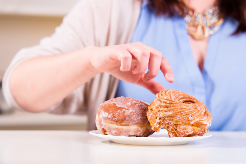 Hand reaches for the sweet donuts on the table in the kitchen