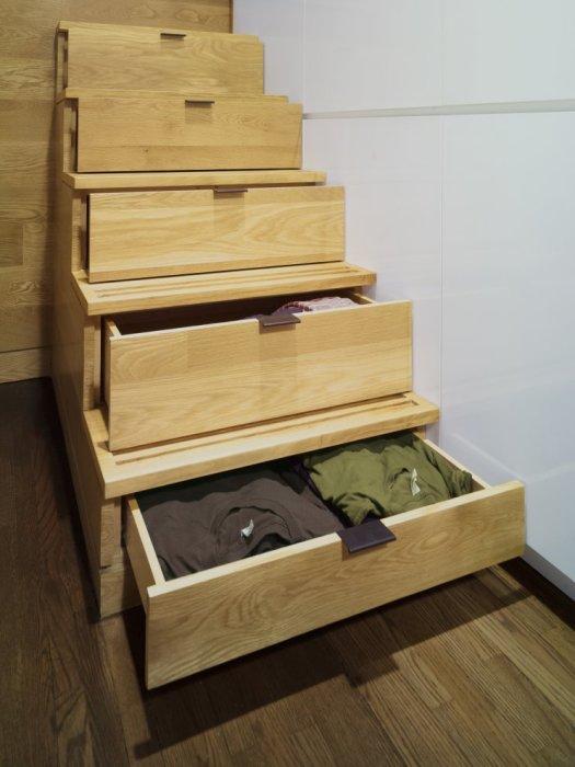 Выдвижные ящики для одежды, вмонтированные под лестничными ступеньками.
